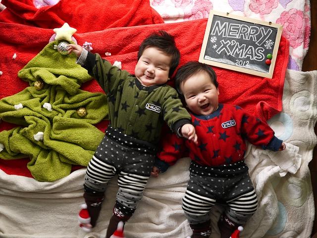 Dve malé deti v teplákoch sa smejú a ležia na posteli.jpg