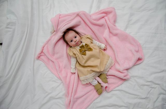 Bábätko v zlatých šatách leží na ružovej deke na posteli.jpg