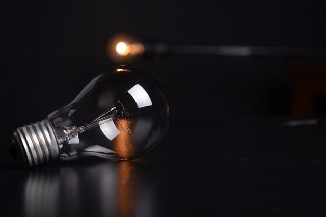 Žiarovka položená na čiernom stole.jpg