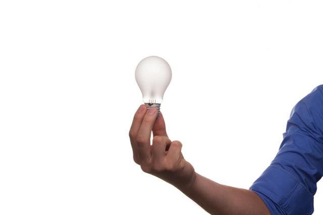 Človek v modrej košeli drží v ruke žiarovku.jpg