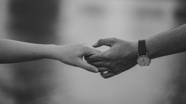 Muž s hodinkami na zápästí drží ženu za ruku.jpg