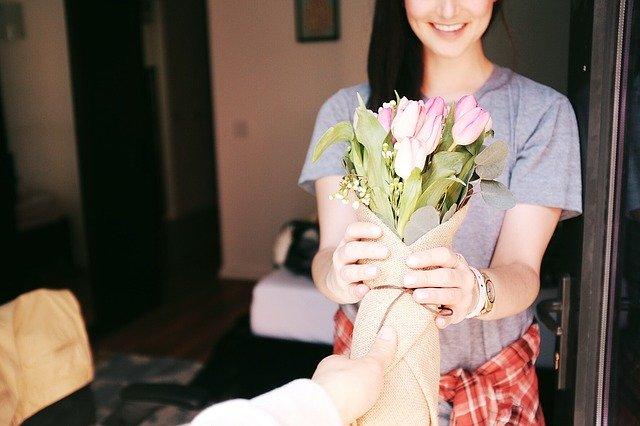 Muž dáva žene kyticu z ružových tulipánov.jpg