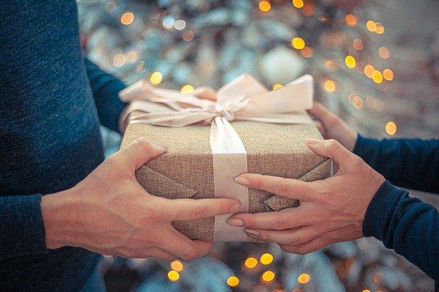 Muž a žena spolu v rukách držia zabalený darček.jpg
