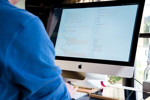Muž v modrej košeli pozerá na obrazovku počítača