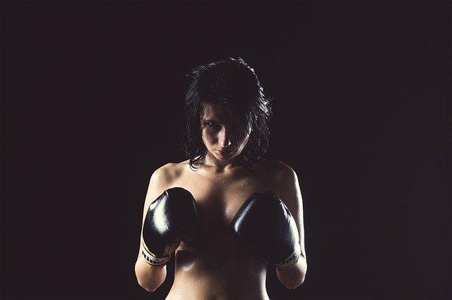 Žena v boxerských rukaviciach si drží ruky pred prsiami